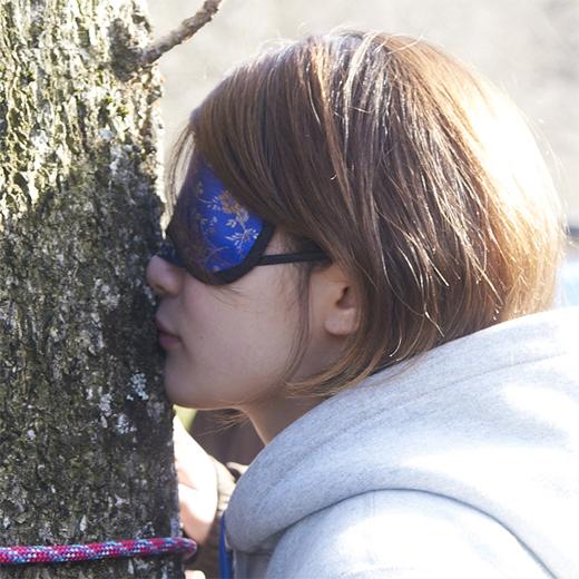 鼻をくっつけて木の表面の匂いをかぐ女性